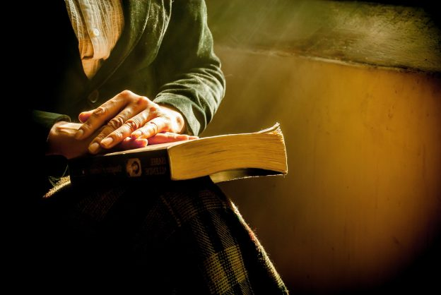 Primer plano de unas manos sobre un libro que está en el regazo de una mujer vestida con una chaqueta verde oscuro