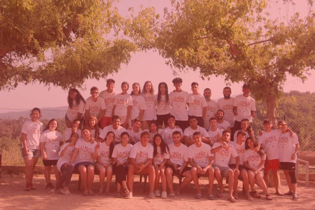 Joves del projecte vitamina posen a un banc d'un parc, tots portes samarretes blanques del projecte