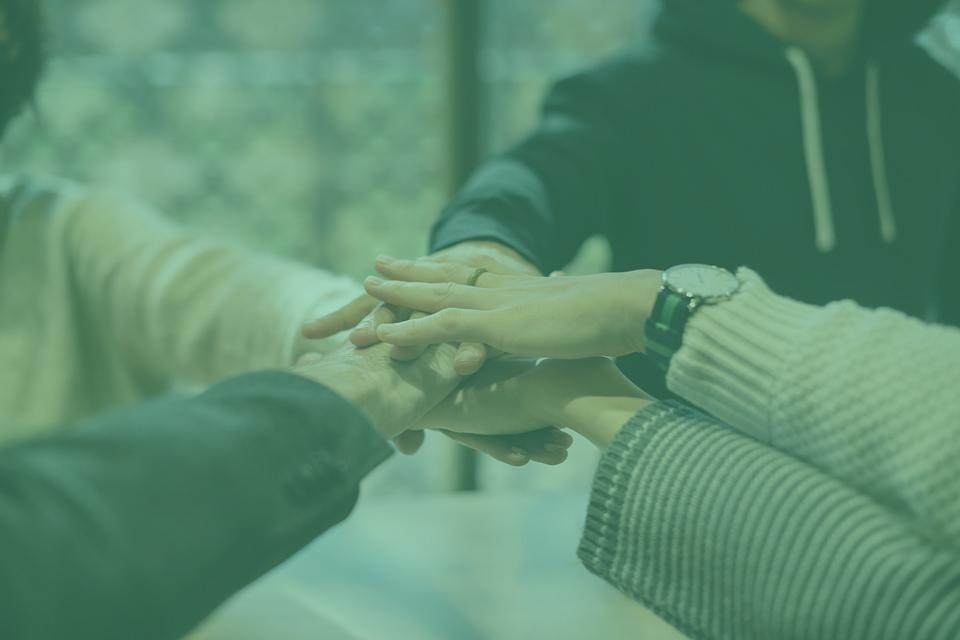 Imatge de mans una sobre l'altra representan el treball en equip