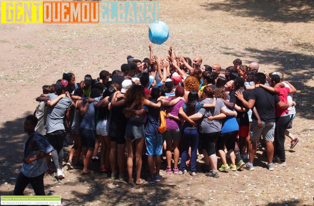 Cartell en el que es veu una rotllana formada per joves i formadors del projecte Vitamina fa volar una pilota amb forma de globus terraqui, escrit hi ha Gent que mou el barri