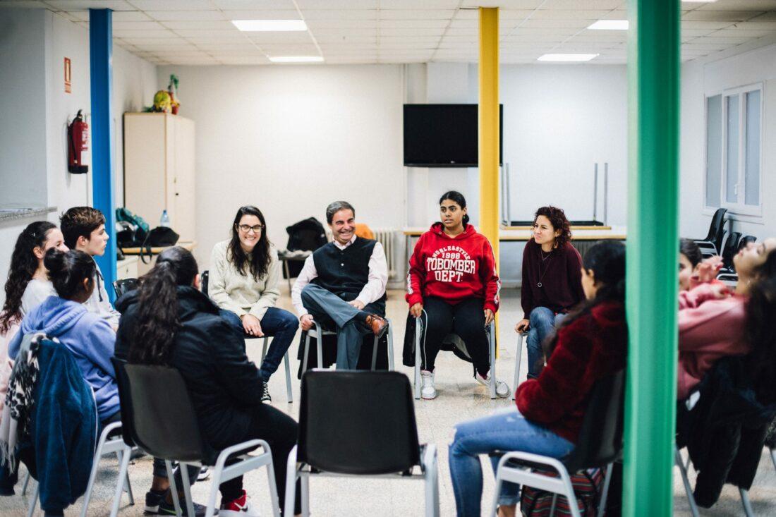 Un grup de joves i dos formadors del projecte Vitamina conversen asseguts en cercle.