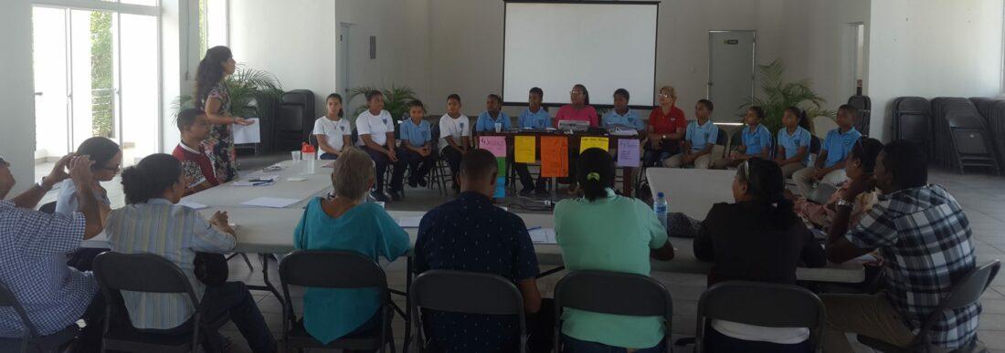 Jornada de formació per a formadors del programa Vitamina T en República Dominicana en la que joves i formadors estan asseguts en taules formant un cercle