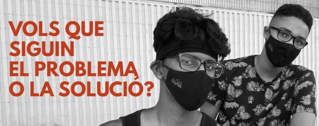 Cartel del projecte Vitamina en el que es veuen dos joves amb ulleres i mascareta, la imatge és en blanc i negreamb lletres taronja.